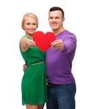 Χαμογελώντας ζεύγος που κρατά τη μεγάλη κόκκινη καρδιά Στοκ Εικόνα
