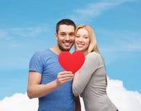 Χαμογελώντας ζεύγος που κρατά τη μεγάλη κόκκινη καρδιά Στοκ Φωτογραφίες