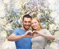 Χαμογελώντας ζεύγος που παρουσιάζει καρδιά με τα χέρια Στοκ φωτογραφίες με δικαίωμα ελεύθερης χρήσης