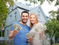 Χαμογελώντας ζεύγος που παρουσιάζει χρήματα πέρα από το υπόβαθρο σπιτιών Στοκ εικόνα με δικαίωμα ελεύθερης χρήσης