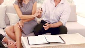 Χαμογελώντας ζεύγος που υπογράφει τη σύμβαση για το καινούργιο σπίτι