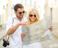 Χαμογελώντας ζεύγος στα γυαλιά ηλίου με το χάρτη στην πόλη στοκ εικόνα με δικαίωμα ελεύθερης χρήσης