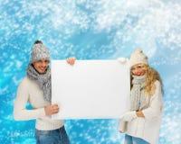 Χαμογελώντας ζεύγος στα χειμερινά ενδύματα με τον κενό πίνακα στοκ φωτογραφίες