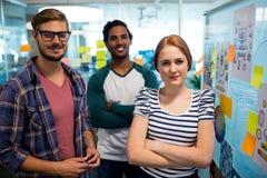 Χαμογελώντας δημιουργική επιχειρησιακή ομάδα που στέκεται δίπλα στις κολλώδεις σημειώσεις στην αρχή Στοκ φωτογραφία με δικαίωμα ελεύθερης χρήσης