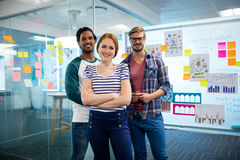 Χαμογελώντας δημιουργική επιχειρησιακή ομάδα που στέκεται ενάντια στις κολλώδεις σημειώσεις στην αρχή Στοκ Εικόνες