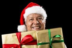 Χαμογελώντας ηλικίας άτομο που κρυφοκοιτάζει σε δύο χρυσά δώρα στοκ φωτογραφίες με δικαίωμα ελεύθερης χρήσης