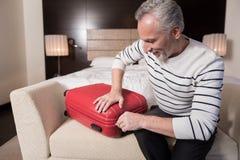 Χαμογελώντας ηλικίας άτομο που προετοιμάζει τις αποσκευές του για ένα ταξίδι Στοκ Εικόνες