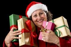Χαμογελώντας ηλικίας γυναίκα που αγκαλιάζει τέσσερα τυλιγμένα δώρα στοκ εικόνα