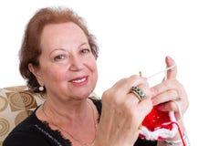 Χαμογελώντας ηλικιωμένη γυναίκα που κάνει την που πλέκει στοκ φωτογραφία