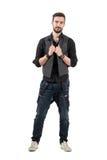 Χαμογελώντας θετικός νεαρός άνδρας που κρατά τη φανέλλα του εξετάζοντας τη κάμερα Στοκ φωτογραφία με δικαίωμα ελεύθερης χρήσης