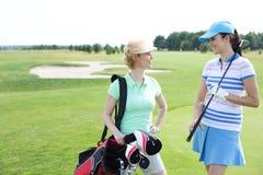 Χαμογελώντας θηλυκοί παίκτες γκολφ που μιλούν στο γήπεδο του γκολφ Στοκ Φωτογραφία