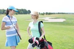 Χαμογελώντας θηλυκοί παίκτες γκολφ που μιλούν στο γήπεδο του γκολφ Στοκ εικόνες με δικαίωμα ελεύθερης χρήσης