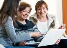 Χαμογελώντας θηλυκοί συνταξιούχοι και σχετικός Ιστός ξεφυλλίσματος στο lap-top Στοκ φωτογραφία με δικαίωμα ελεύθερης χρήσης