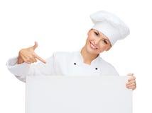 Χαμογελώντας θηλυκός αρχιμάγειρας με το λευκό κενό πίνακα Στοκ εικόνες με δικαίωμα ελεύθερης χρήσης