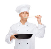 Χαμογελώντας θηλυκός αρχιμάγειρας με το τηγάνι και το κουτάλι Στοκ φωτογραφία με δικαίωμα ελεύθερης χρήσης