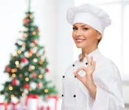 Χαμογελώντας θηλυκός αρχιμάγειρας που παρουσιάζει εντάξει σημάδι Στοκ Φωτογραφία