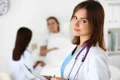 Χαμογελώντας θηλυκός γιατρός ιατρικής που γεμίζει το υπομονετικό ιατρικό ιστορικό λ Στοκ Εικόνα