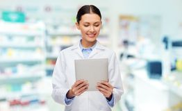 Χαμογελώντας θηλυκός γιατρός με το PC ταμπλετών στο φαρμακείο στοκ φωτογραφία