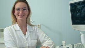 Χαμογελώντας θηλυκός γιατρός που εξετάζει τη κάμερα και που παίρνει τα γυαλιά της μακριά απόθεμα βίντεο