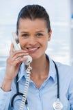 Χαμογελώντας θηλυκός γιατρός που μιλά στο τηλέφωνο Στοκ Εικόνες