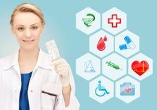 Χαμογελώντας θηλυκός γιατρός που παρουσιάζει πακέτο των χαπιών Στοκ Εικόνα