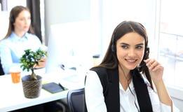 Χαμογελώντας θηλυκός κεντρικός χειριστής κλήσης που κάνει την εργασία της με μια κάσκα εξετάζοντας τη κάμερα Στοκ Εικόνες