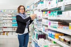 Χαμογελώντας θηλυκός πελάτης που επιλέγει το προϊόν στοκ εικόνες με δικαίωμα ελεύθερης χρήσης