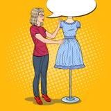 Χαμογελώντας θηλυκός σχεδιαστής μόδας με το φόρεμα σε ένα μανεκέν clothing dummies female industry inside store textile women Λαϊ απεικόνιση αποθεμάτων