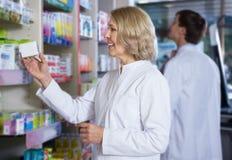 Χαμογελώντας θηλυκός φαρμακοποιός στο φαρμακείο στοκ εικόνα με δικαίωμα ελεύθερης χρήσης