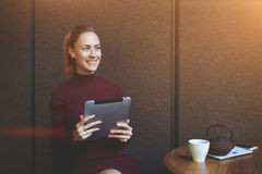 Χαμογελώντας θηλυκό που σκέφτεται για κάτι θετικό κατά τη διάρκεια της εργασίας για την ψηφιακή ταμπλέτα Στοκ φωτογραφίες με δικαίωμα ελεύθερης χρήσης