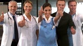 Χαμογελώντας ιατρική ομάδα με τους αντίχειρες επάνω φιλμ μικρού μήκους