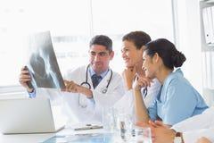 Χαμογελώντας ιατρική ομάδα που αναλύει την ακτίνα X στοκ φωτογραφίες