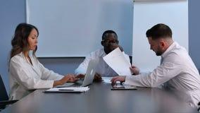 Χαμογελώντας ιατρική ομάδα που χρησιμοποιεί το lap-top για να εργαστεί, συζητώντας τη νέα ιατρική απόθεμα βίντεο