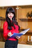 Χαμογελώντας διευθυντής στην κόκκινη μπλούζα με έναν φάκελλο των εγγράφων στο θόριο Στοκ εικόνες με δικαίωμα ελεύθερης χρήσης