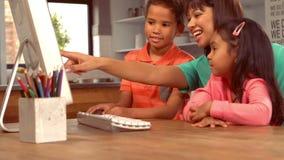 Χαμογελώντας ισπανική μητέρα στον υπολογιστή με τα παιδιά της απόθεμα βίντεο