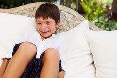 Χαμογελώντας ισπανικό αγόρι που κάθεται στο σπίτι σε υπαίθριο Seatï ¿ ½ Στοκ Εικόνες