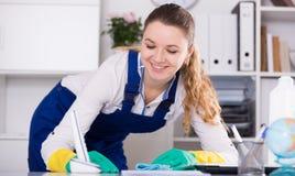 Χαμογελώντας καθαρίζοντας δωμάτιο γυναικών στοκ εικόνες