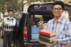 Χαμογελώντας και ανοίγοντας αυτοκίνητο αγοριών για το κολλέγιο, που κρατά τα βιβλία Στοκ Εικόνες