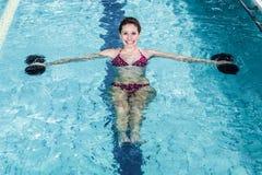 Χαμογελώντας κατάλληλη γυναίκα που κάνει τη αερόμπικ aqua Στοκ Εικόνες