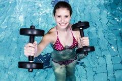 Χαμογελώντας κατάλληλη γυναίκα που κάνει τη αερόμπικ aqua Στοκ Φωτογραφίες