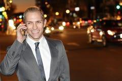 Χαμογελώντας καυκάσιος επιχειρηματίας που καλεί τηλεφωνικώς στην οδό τη νύχτα - εικόνα αποθεμάτων Στοκ εικόνες με δικαίωμα ελεύθερης χρήσης