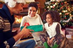 Χαμογελώντας καλό κορίτσι που λαμβάνει το χριστουγεννιάτικο δώρο από τους γονείς στοκ εικόνες