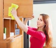 Χαμογελώντας κοκκινομάλλης γυναίκα που καθαρίζει το ξύλινο furiture Στοκ εικόνα με δικαίωμα ελεύθερης χρήσης