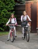 Χαμογελώντας κορίτσια στην ομοιόμορφη οδήγηση στο σχολείο στα ποδήλατα Στοκ Εικόνες