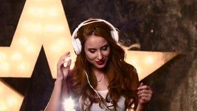 Χαμογελώντας κορίτσι εφήβων με τα ακουστικά στο στούντιο μουσικής απόθεμα βίντεο