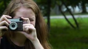 Χαμογελώντας κορίτσι εφήβων με την αναδρομική κάμερα φιλμ μικρού μήκους