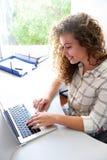 Χαμογελώντας κορίτσι εφήβων με το lap-top στην αρχή Στοκ φωτογραφία με δικαίωμα ελεύθερης χρήσης