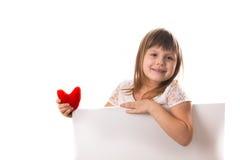 Χαμογελώντας κορίτσι με έναν πίνακα για το γράψιμο και μια κόκκινη καρδιά στο han της Στοκ Εικόνες