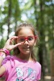 Χαμογελώντας κορίτσι με τα κόκκινα γυαλιά Στοκ Εικόνα
