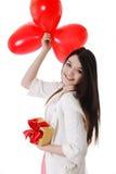 Χαμογελώντας κορίτσι με τα κόκκινα μπαλόνια και το δώρο Στοκ Εικόνες